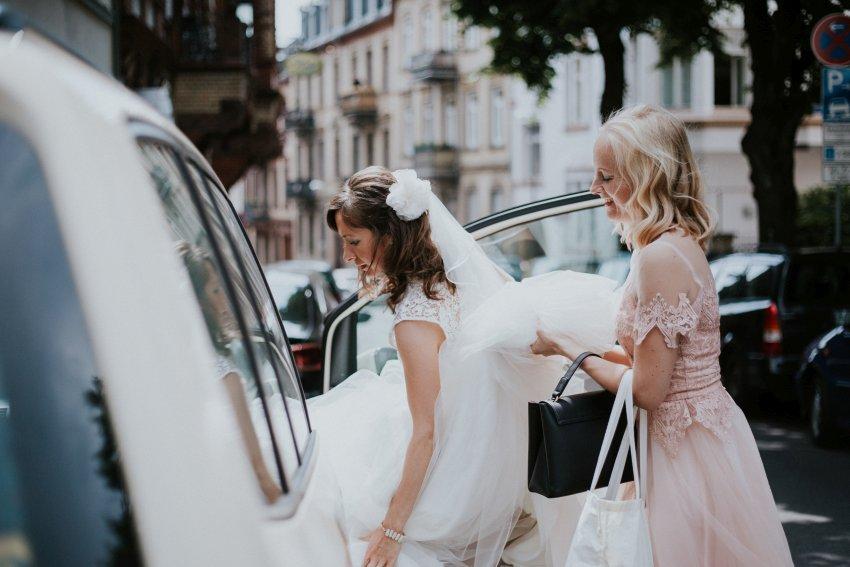 Trauzeugin hilft Braut beim Einsteigen ins Auto