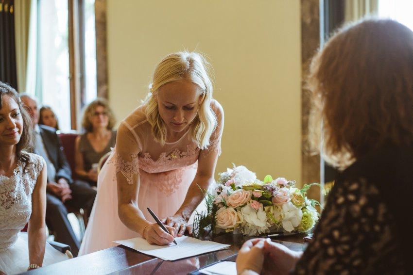 Trauzeugin unterschreibt für die Braut im Standesamt